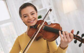 Cheerful girl playing a violin bow\