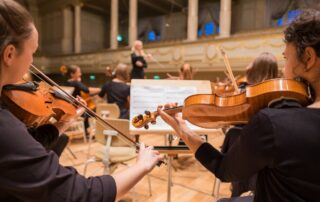 string orchestra playing in front of a conductor